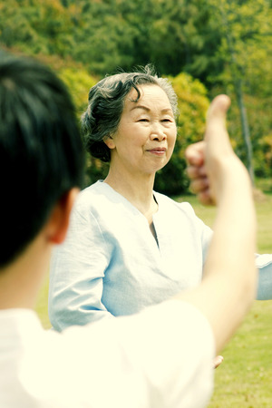 A boy giving his grandmother a thumb up for performing a good tai chi technique in the park Stock Photo