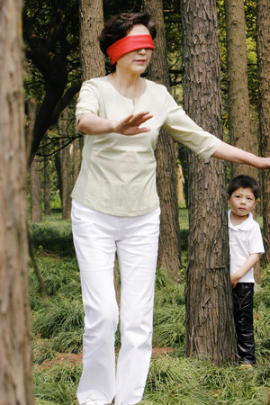 blindfolded: A boy hiding behind a tree as his blindfolded grandmother searching for him Stock Photo