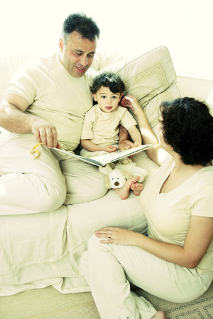 A man sitting on the couch reading a story book for his young son while his wife watching photo