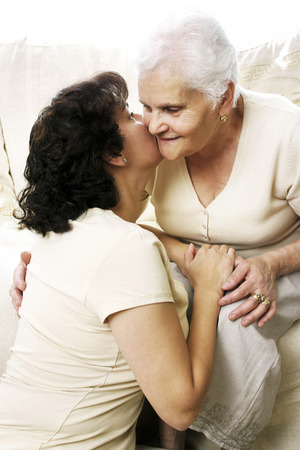 peck: A woman giving her old mother a peck on the cheek