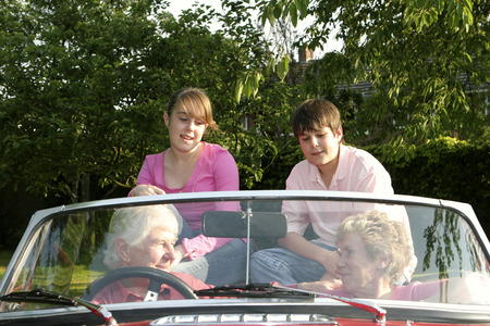 An old couple taking their grandchildren for a car ride photo