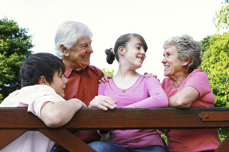 A boy and a girl standing near the wooden fence with their grandparents photo