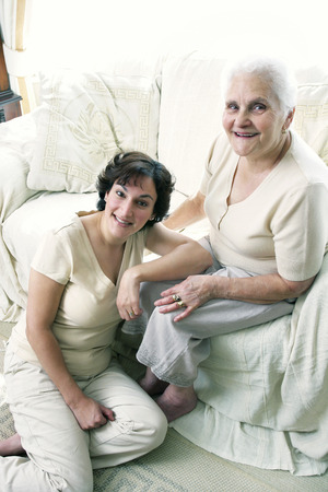 cherishing: A woman sitting on the floor while her old mother is sitting on the couch Stock Photo