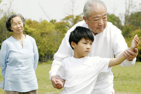 An old man teaching his grandson tai chi techniques while his wife is watching