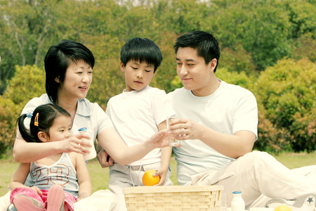 A family picnicking in the park photo