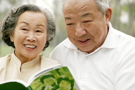 An old couple sharing a book Stock Photo