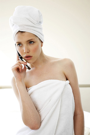 hair wrapped up: A woman with her hair and body wrapped up in towel talking on the hand phone Stock Photo