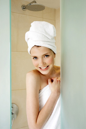 A woman with her hair and body wrapped up in towel hiding behind the shower door