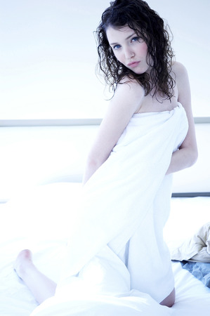 hair wrapped up: A woman with wet hair and body wrapped up in towel kneeling on the bed