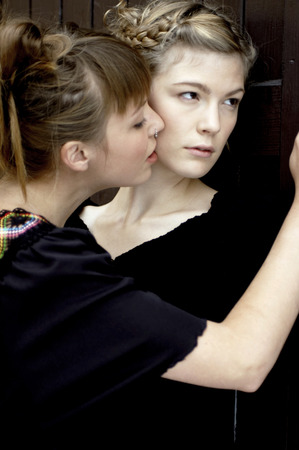 smooching: A woman pressing her partner against the door while sniffing her cheek