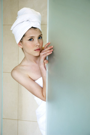 playful behaviour: A woman with her hair and body wrapped up in towel hiding behind the shower door