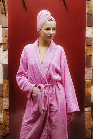 towel wrapped: A lady in pink robe and towel wrapped hair standing with her hand in the pocket Stock Photo
