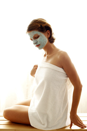 A woman with facial mask wrapping a towel around her body photo
