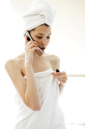 A woman with her hair and body wrapped up in towel talking on the hand phone in the bathroom photo