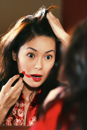 oriental bathrobe: A woman in oriental bathrobe overdrawing her lipstick out of her lips
