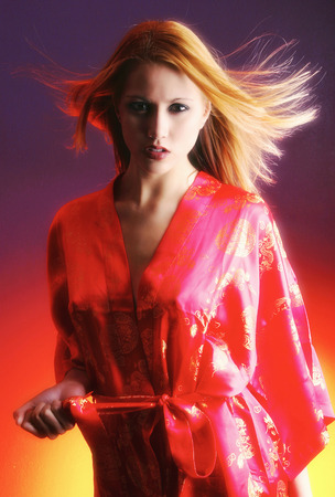 red bathrobe: Studio shot of a woman in red bathrobe staring seductively at the camera Stock Photo