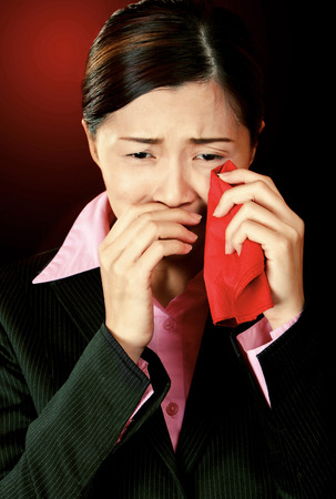 A lady in formal suit wiping her tears with a red handkerchief photo