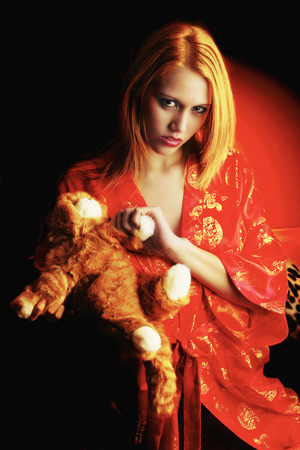 red bathrobe: A woman in red bathrobe holding a soft toy Stock Photo
