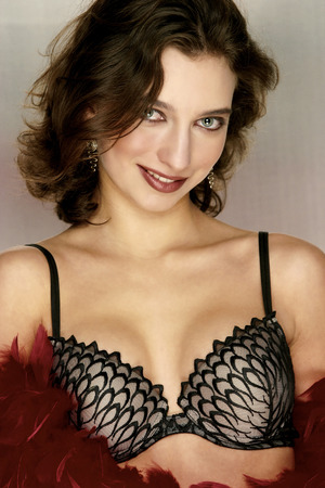 female model: A female model in black and white bra holding red feathers and flashing a smile at the camera