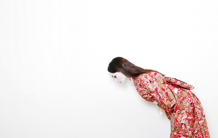 side shot of a woman in red kimono bowing  Reklamní fotografie