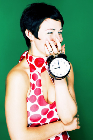Woman in red and white polka dots dress holding a clock  photo