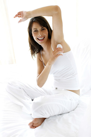 underarm: Woman smiling while applying antiperspirant onto her underarm  Stock Photo