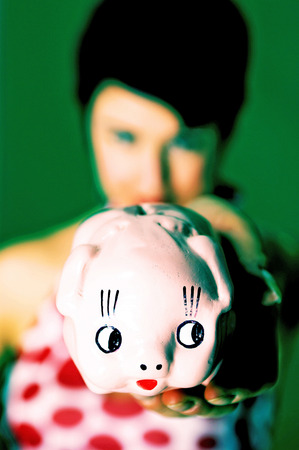 Woman in red and white polka dots dress showing a piggy bank  photo