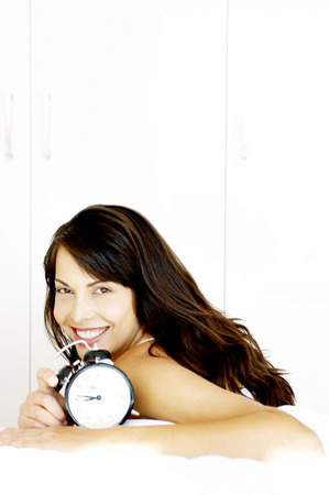 Woman smiling while showing a clock photo
