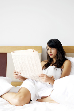 Woman in towel reading newspaper on the bed  photo