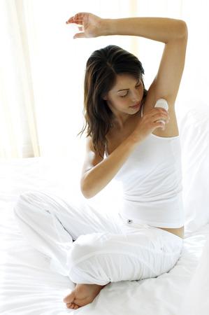 underarm: Woman applying antiperspirant onto her underarm