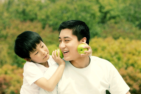 A boy playfully placing two green apples on his father's cheeks photo