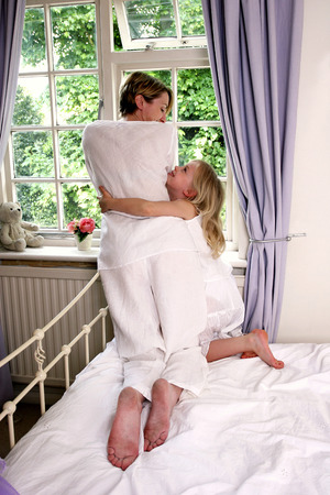 A girl hugging her mother who is looking out from the bedroom window photo