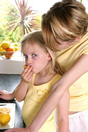 safekeeping: A woman watching her daughter eating lemon