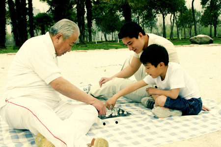 A boy playing chess with his grandfather on the lakeside while his father is watching photo
