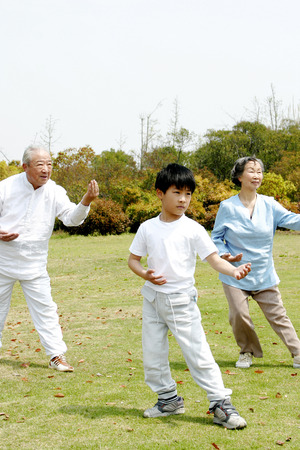 asian art: A boy practicing tai chi with his grandparents in the park Stock Photo