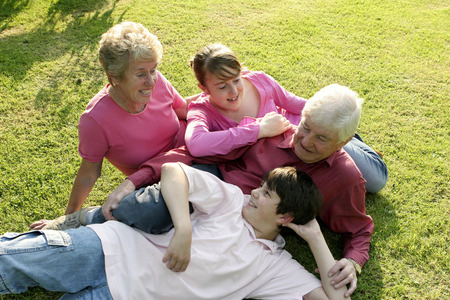 An old couple lying together with their grandchildren on the field
