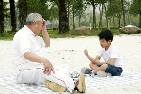 A boy playing chess with his grandfather on the lakeside photo