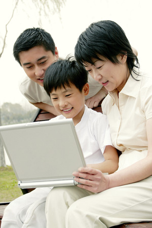 A woman and her son sitting on the bench using laptop while her husband standing behind them photo