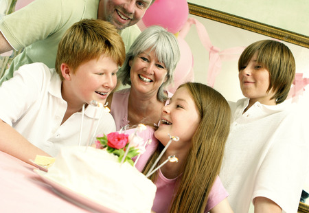 he   my sister: A girl sitting in front of her birthday cake with her parents and siblings surrounding her Stock Photo