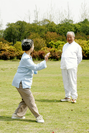 An old man watching his wife practicing tai chi in the park photo