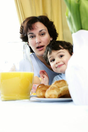 A young boy sitting on his mothers lap having breakfast photo
