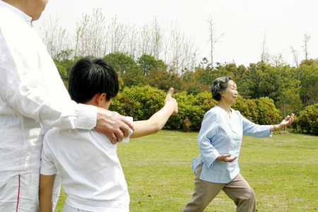 A boy giving his grandmother a thumb up for performing a good tai chi technique in the park photo