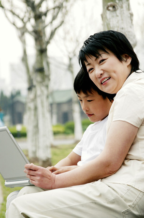 Side shot of a woman and her son sitting on the bench with a laptop on their laps photo