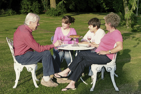 A boy and a girl talking to their grandparents in the garden photo