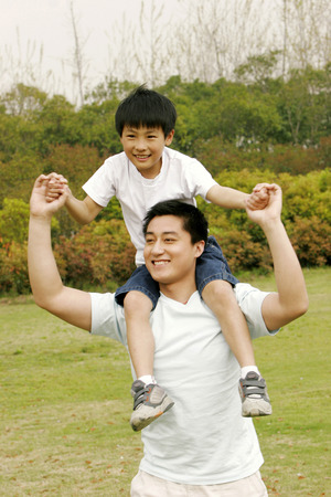 A man giving his son a piggy back ride in the park Stock Photo