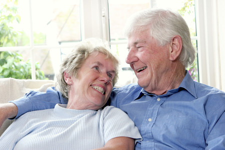 adoring: An old man sitting on the couch with his arm around his wife