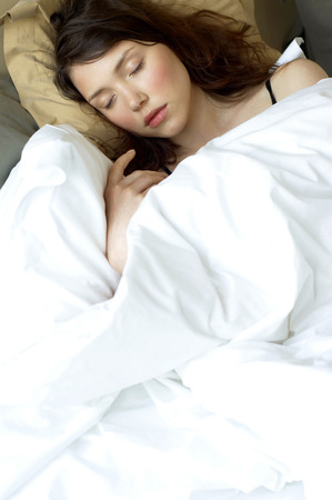 A woman covered with blanket sleeping on the bed photo