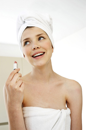 hair wrapped up: A woman with her hair and body wrapped up in towel holding a lipstick