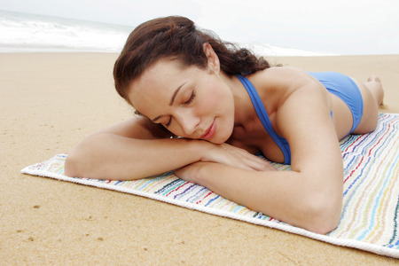 blue bikini: A lady in blue bikini lying on her front with her eyes closed