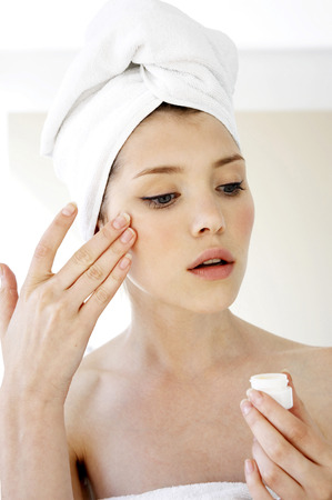 A woman with her hair and body wrapped up in towel applying under eye cream